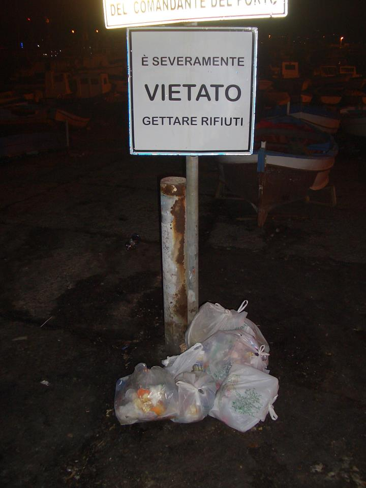 "I took this picture recently while taking an evening stroll along the sea front. The sign says ""It is STRICTLY forbidden to throw rubbish here."" .....Ah, these Sicilians!"