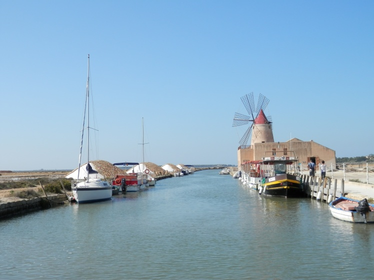 Salt works at Marsala. The windmill you can see is used for milling very large salt rocks into smaller pieces.  on the left you can see heaps of salt, protected from the rain by terracotta roof tiles. The salt extracted from the sea is left like this for the 6 winter months to continue drying out.