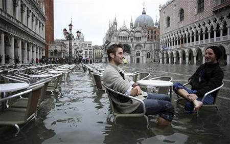 English tourists in St. Mark's Square, Venice; they haven't actually noticed the adverse weather conditions.