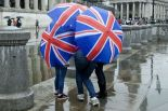 Tourists-seek-shelter-from-the-rain-in-Trafalgar-Square